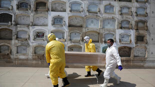 Funerarios llevan un ataúd con el cuerpo de una persona que murió de la enfermedad coronavirus (COVID-19), en un cementerio de Lima, Perú, el 9 de mayo de 2020. REUTERS/Sebastián Castaneda.
