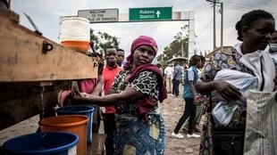 A woman washes her hands at an Ebola control post before entering the DRC from Rwanda, 16 July 2019.