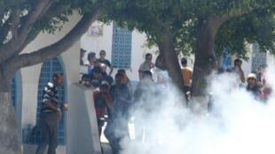 Des partisans salafistes sous les tirs de gaz lacrymogènes à Kairouan, le 19 mai 2013.