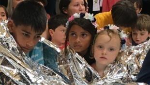 Des enfants sont assis au milieu des manifestants revêtus de couvertures de survie pour représenter les jeunes migrants séparés de leurs parents en centre de rétention à la frontière mexicaine.