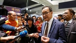 Cambodia's self-exiled opposition party founder Sam Rainsy, who has vowed to return to his home country, talks to supporters after being prevented from checking in for a flight from Paris to Bangkok at Roissy Airport in Paris