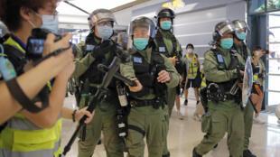 Un policier anti-émeute repousse le micro d'un journaliste avec sa matraque lors d'une manifestation à Hong Kong, le 21 juillet 2020.