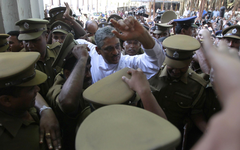 Au Sri Lanka, l'ancien chef des armées, Sarath Fonseka, entouré des policiers arrive au tribunal, à Colombo, le 18 novembre 2011.