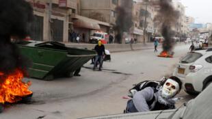 Manifestantes palestinos atiram pedras contra forças israelenses em Ramallah, Cisjordânia.