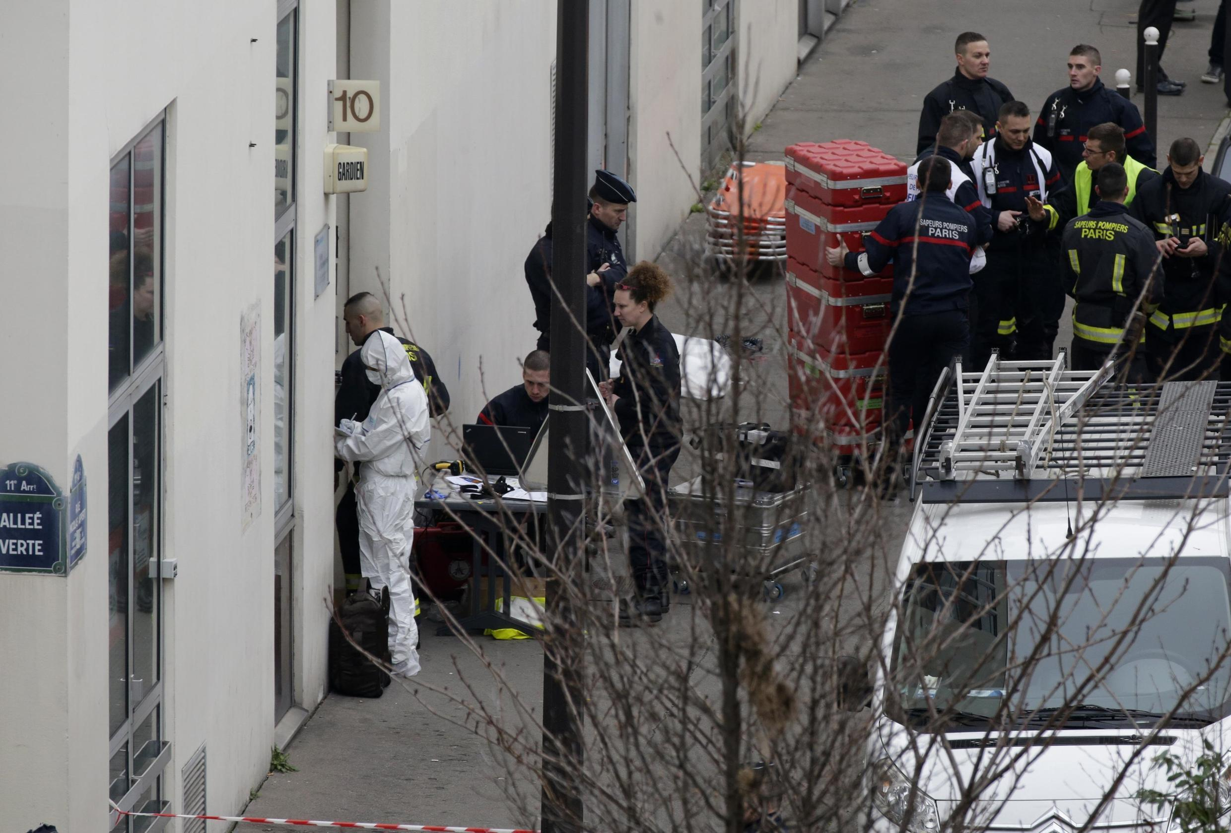 Police investigators and firefighters in front of the Paris offices of Charlie Hebdo after the attack