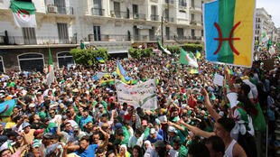Demonstrators in Algiers, Algeria, holding an Amazigh flag at a 21 June 2019 protest.