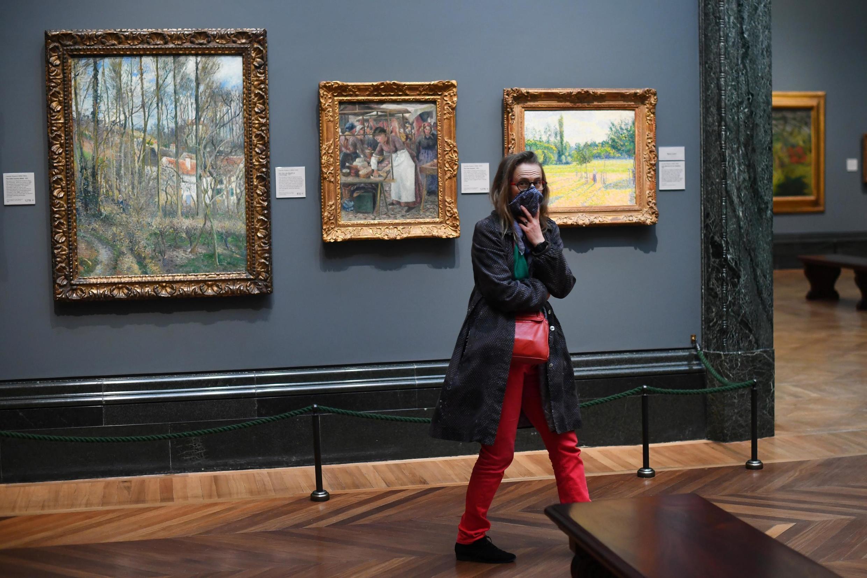 Une touriste couvre son visage dans la National Gallery quelques minutes avant sa fermeture pour endiguer l'épidémie de coronavirus. Londres, le 18 mars 2020.