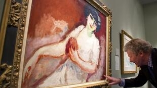 Un visiteur examine le tableau «Femme rose sur fond rouge» de Kees van Dongen à la Tefaf de Maastricht, le 12 mars 2015.