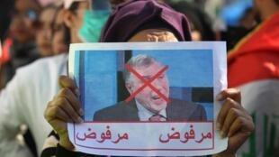Une femme irakienne tient dans la main une photo du Premier ministre Mohammed Allawi avec l'inscription «rejeté», lors d'une manifestation anti-gouvernementale à Bagdad, le 4 février 2020.