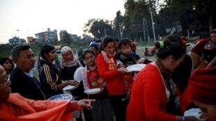 Desplazados hacen cola para comer en una distribución de alimentos organizada por una ONG nepalesa en Katmandú, 27 de abril de 2015.