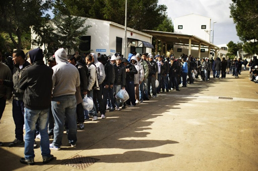 Tunisian migrants queue in front of a temporary camp on the Italian island of Lampedusa.