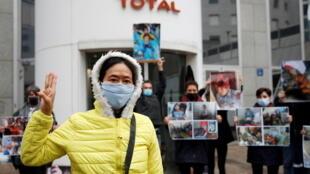 Une militante d'«Extinction Rebellion» fait le geste des trois doigts (symbole des manifestants birmans) avec d'autres militants tenant des photos des victimes du coup d'État militaire en Birmanie lors d'une manifestation devant le siège de Total, dans le quartier d'affaires de La Défense, près de Paris, en France, le 25 mars 2021.