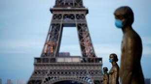 Les statues de l'esplanade des droits de l'homme sur la place du Trocadéro à Paris près de la tour Eiffel portent des masques de protection, le 2 mai.