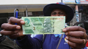 Une femme zimbabwéenne montre son  avoir en dollars américains en dehors d'une banque dans la capitale Harare, au Zimbabwe, le 28 novembre 2016.