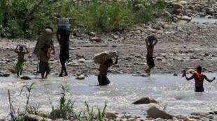 La frontière entre le Venezuela et la Colombie, longue de 2 000 km, est difficile à contrôler. Ici des contrebandiers traversent la rivière Tachira qui sépare la Colombie du Venezuela.