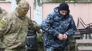Un membre du service de sécurité russe FSB escorte un des 12 marins ukrainiens au tribunal de Simféropol, le chef-lieu de la Crimée, le 27 novembre 2018.