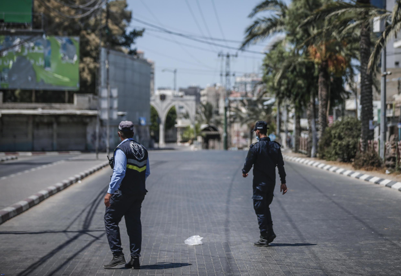 Policías palestinos patrullan una calle de la ciudad de Gaza en medio del toque de queda de dos días debido a la detección de los primeros casos de COVID-19 en la población, el 25 de agosto de 2020