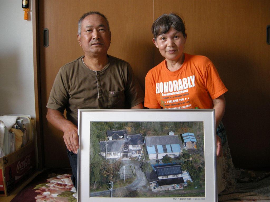 Monsieur et Madame Watanabe, 65 et 62 ans, agriculteurs bio évacués de la ville d'Okama près de la centrale de Fukushima, montrent une photo de la maison qu'ils ont abandonnée.