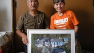 El Sr. y la Sra. Watanabe, que fueron evacuados de Okama, ciudad cercana a la central de Fukushima, muestran una foto de su casa.