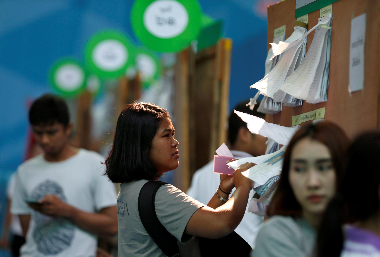 Cử tri xem danh sách ứng cử viên tại một phòng phiếu ở Bangkok ngày 17/03/2019.