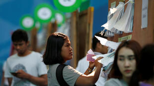Les Thaïlandais consultent la liste des candidats aux prochaines élections législatives dans un bureau de vote à Bangkok, le 17 mars 2019.