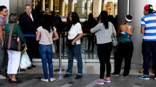 Des Vénézuéliens patientent devant un centre commercial fermé durant la semaine sainte fériée, le 10 février 2016 à Caracas.