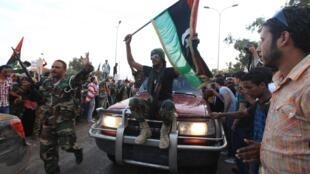 Combatantes anti-Kadafi que retornam de Syrte são acolhidos pela população de Benghazi.