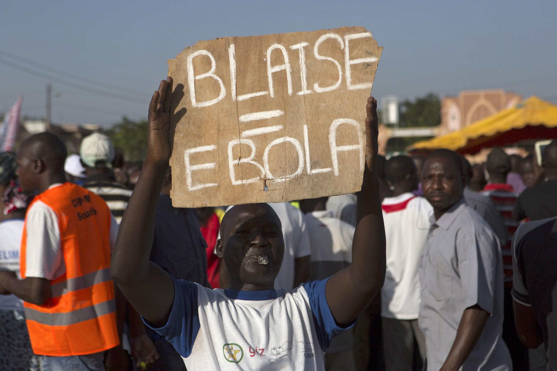 Wani mai zanga-zanga dauke da wani allon da aka rubuta kalaman adawa da Shugaban Burkina Faso Blaise Compaore