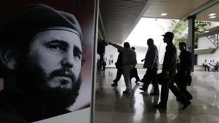 Des délégués du Congrès du Parti Communiste cubain passent devant un portrait de Fidel Castro.