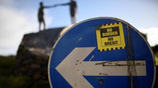 北爱尔兰境内写着握手超越分离的和平雕塑附近公路上,一个方向路牌上贴着一则宣传标语:不要边界,不要脱欧。摄于2019年1月22日。
