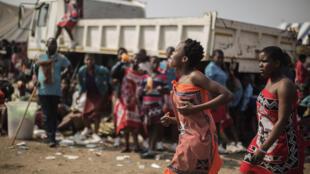 Au Swaziland, les jeunes filles descendent des camions pour se préparer à la danse des roseaux.