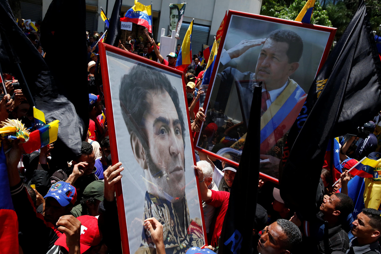 Des partisans du président Nicolas Maduro devant le Palais fédéral législatif où se tient la séance inaugurale de la Constituante, en arborant des portraits de l'ex-président Hugo Chavez et du héros national Simon Bolivar, à Caracas, le 4 août 2017.