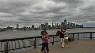 Des passants se mettent à l'abri du vent sur les bords de l'Hudson.