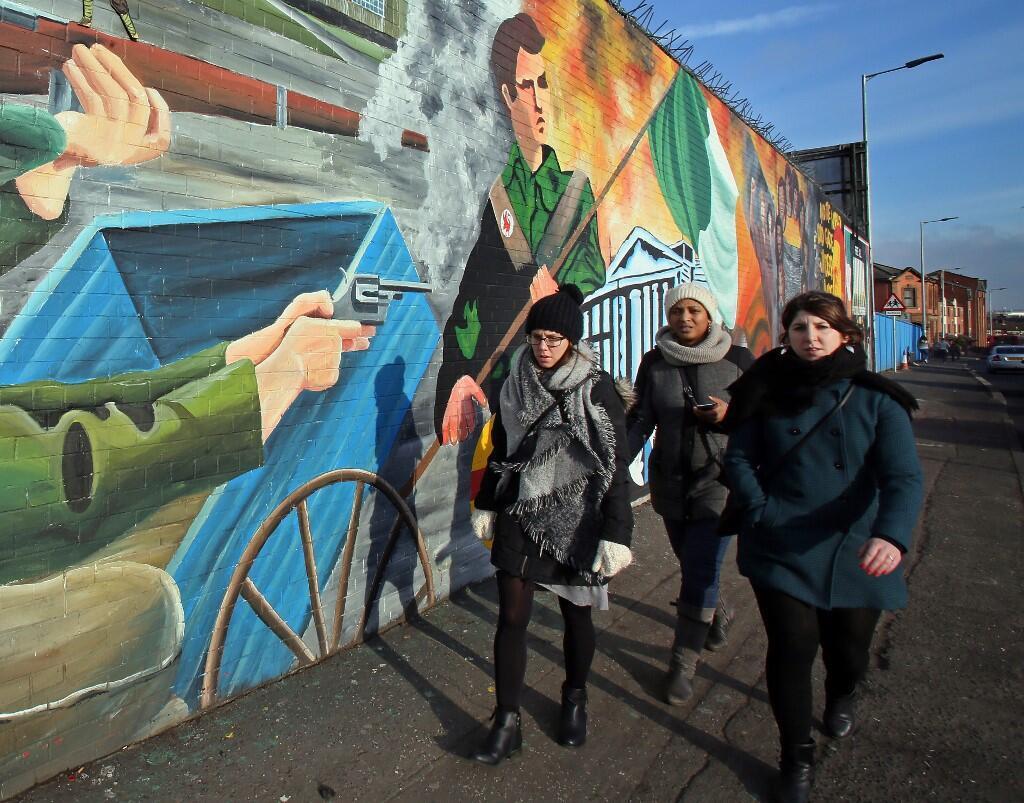 Passantes devant des peintures murales évoquant la guerre en Irlande du Nord, sur Falls road, dans l'ouest de Belfast.