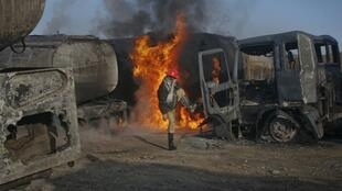 A firefighter kicks close the door of a fuel truck which was set ablaze in Quetta, Pakistan