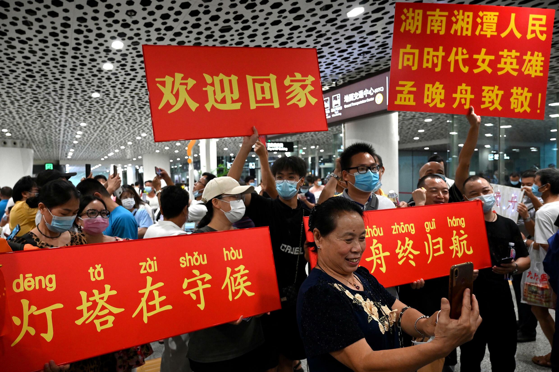 Un grupo de personas  espera la llegada de la alta ejecutiva de la empresa de telecomunicaciones china Huawei, Meng Wanzhou, al Aeropuerto Internacional Bao'an, en Shenzhen, China, el 25 de septiembre de 2021.