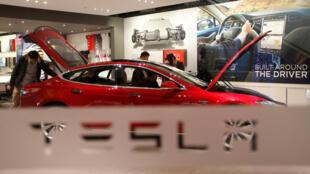 Un homme regarde une voiture Tesla ( constructeur automobile de voitures électriques sportives et de luxe) dans un magasin de Pékin, en Chine.