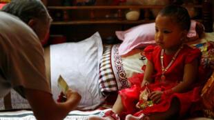 """Homem oferece dinheiro para a nova """"deusa viva"""" do Nepal, Trishna Shakya, de apenas três anos de idade."""