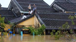 Pessoas esperam socorro em cima do telhado, numa rua de Hoi An, património mundial da Unesco, depois da passagem do tufão Damrey, a 6 de Novembro de 2017.