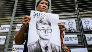 Un protestataire arborant un portrait de Simon Cheng, en août 2019 à Hong Kong.