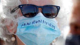 """A woman wearing a protective face mask with the slogan """"Macronavirus"""" attends a demonstration urging the French government to provide more means and better working conditions to health workers on May 28, 2020."""