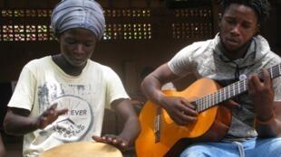 A Ouagadougou, deux anciens enfants des rues initient les enfants à la musique, lors d'ateliers proposés par l'association ATD Quart Monde.