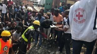 Jami'an agajin da ke lalubo kananan yaran da suka makale a benen bayan ruguzowarsa yau a Lagos