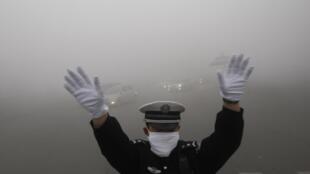 Guarda de transito nas ruas de Harbin, na China em um dia muito poluido.
