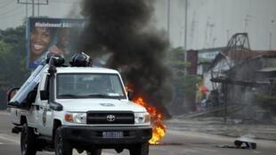 Police drive past burning tires in Democratic Republic of Congo's capital Kinsh