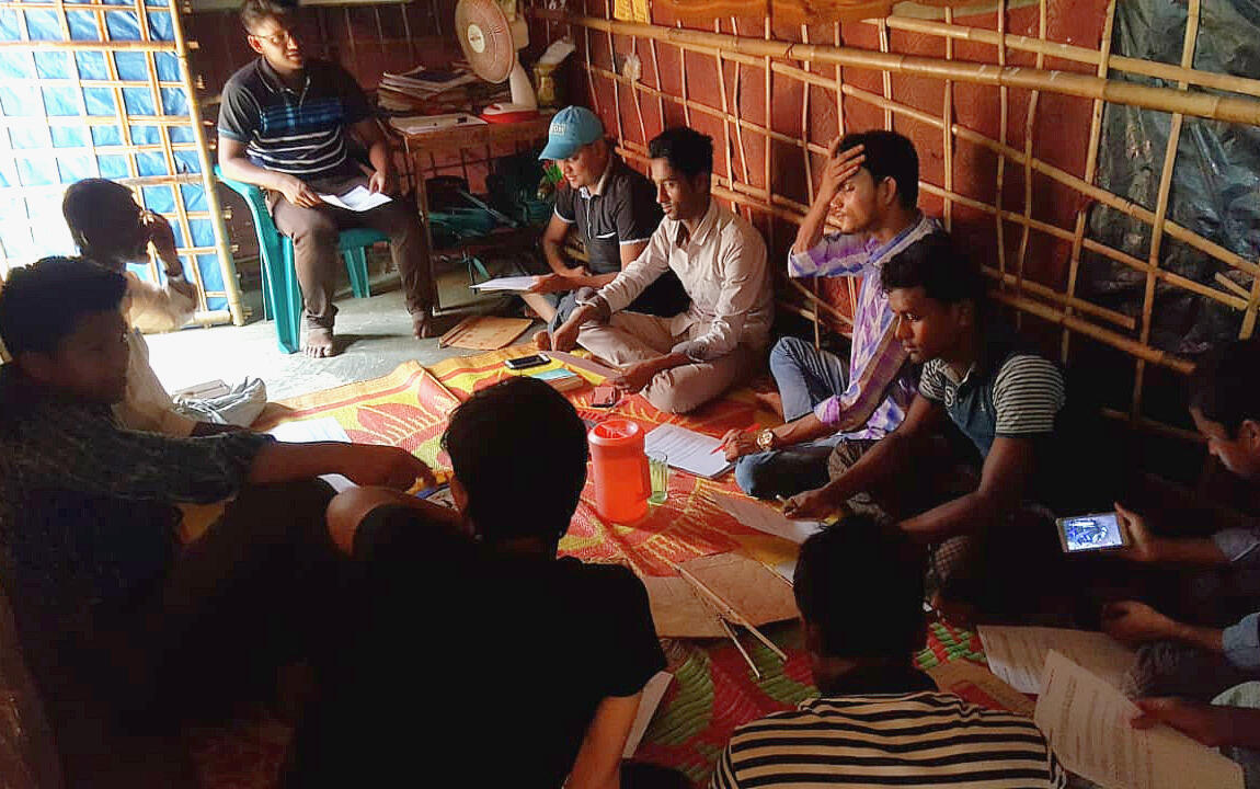 Khin Maung with a group of teachers preparing exam papers.