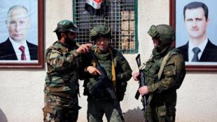 Soldats russes et syriens près du poste de contrôle de Wafideen à Damas, en Syrie, le 2 mars 2018.