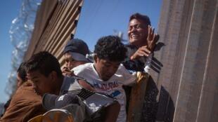Wahamiaji wakijaribu kuvuka ukuta wa mpaka kinyume cha sheria kwenda Marekani huko Tijuana, Mexico.