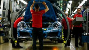 Des ouvriers assemblent une voiture dans une usine Porsche de Stuttgart, le 25 mai 2018.