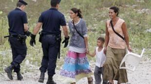 Ciganos originários do leste europeu são evacuados de acampamento ilegal perto de Lyon, na França, nesta terça-feira.
